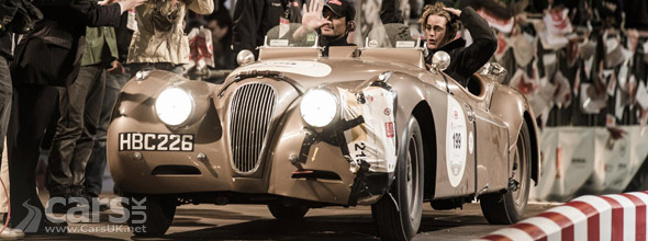 Yasmil Le Bon & David Gandy crossing the finish line in a Jaguar XK120 at the 2013 Mille Miglia