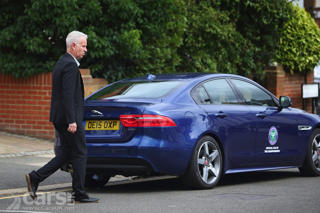 ?John McEnroe walking towards his Jaguar XE