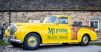A yellow Bentley S1 Pick-up with wood load bed
