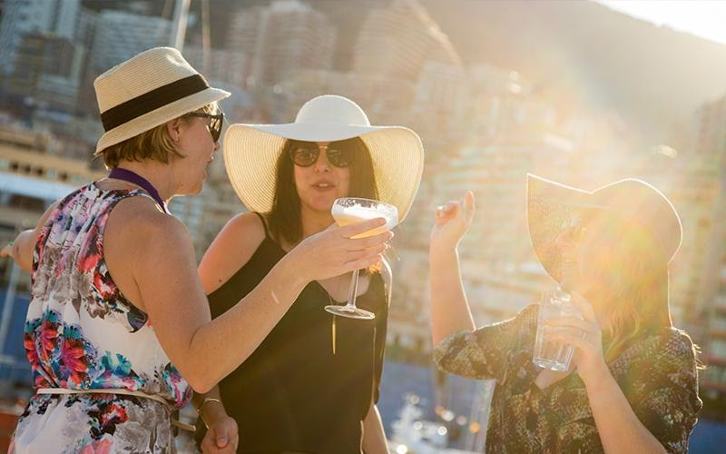 A group of women enjoying conversation and cocktails on the Monaco waterfront on a sunny day