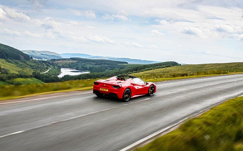 A red Ferrari drives across the English countryside on an overcast day