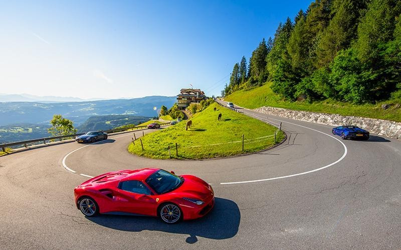 A red Ferrari drives around a hairpin bend on a green hillside on a sunny day