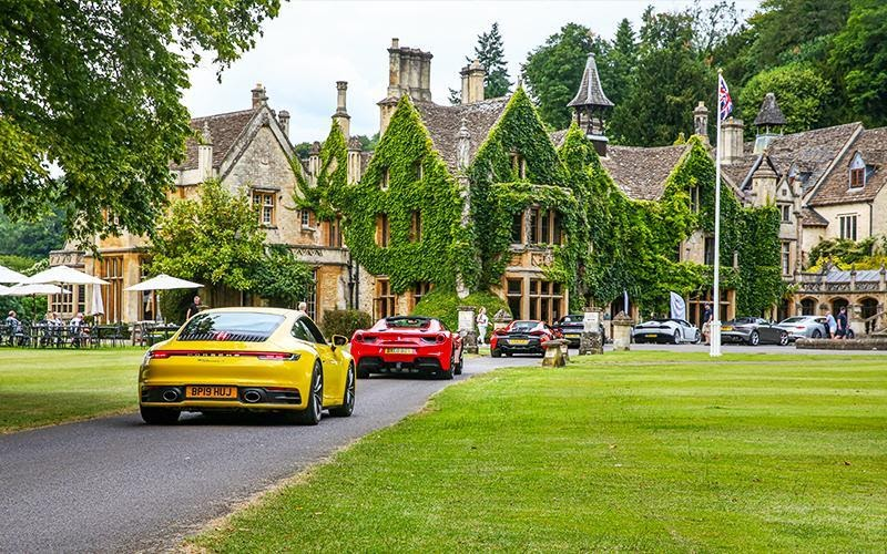A line of modern supercars arriving at an opulent British country Manor